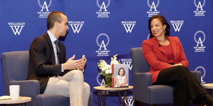 Susan Rice talks to a Wellesley professor in front of a blue backdrop