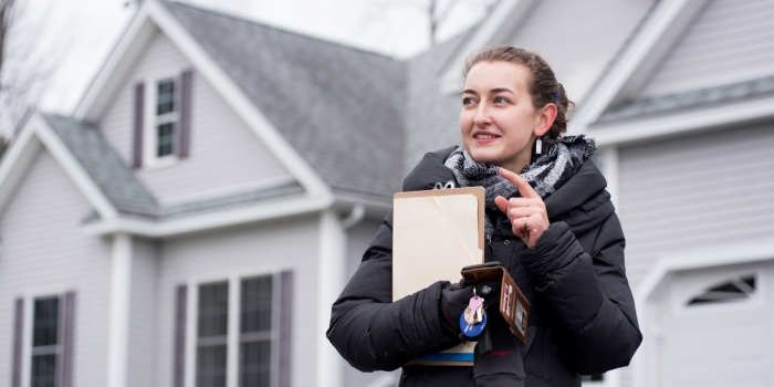 An alumna stands in front of a gray house with a clipboard
