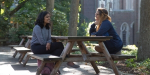 Two students sit at picnic tables in the academic quad.