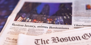 """The front page of the Boston Globe, which reads """"Boston Luxury, Minus Bostonians."""""""