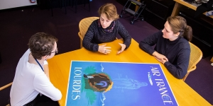 Three people look at a blue poster depicting the Virgin Mary