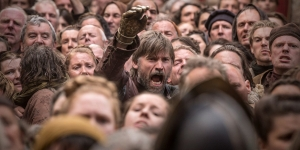 Game of Thrones character Jamie Lanister reaches from a crowd of peasants as he fights to break through.