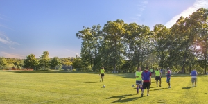 Staff and faculty play soccer outside.