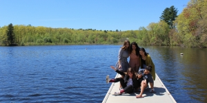 Students stand on a dock by Lake Waban preparing to take a photo.