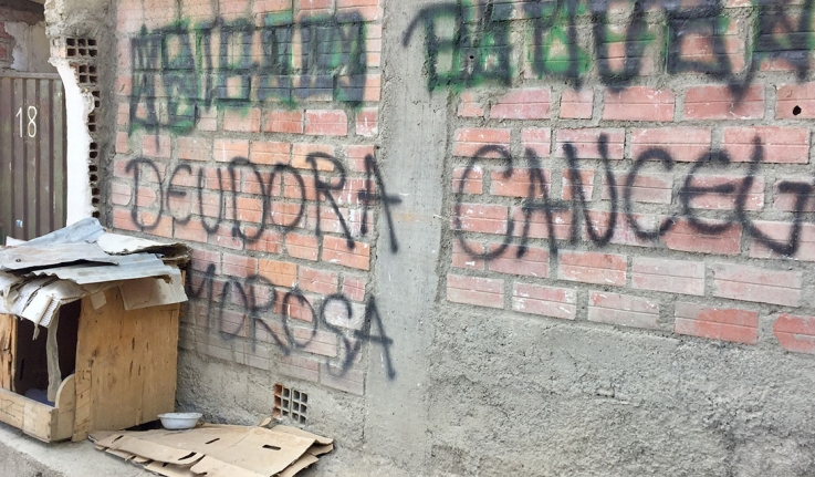 """Graffiti on the wall of a house, which reads """"Deudor moroso"""""""