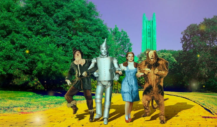 Characters from the Wizard of Oz stand on the yellow brick road in front of emerald green Galen Stone Tower.