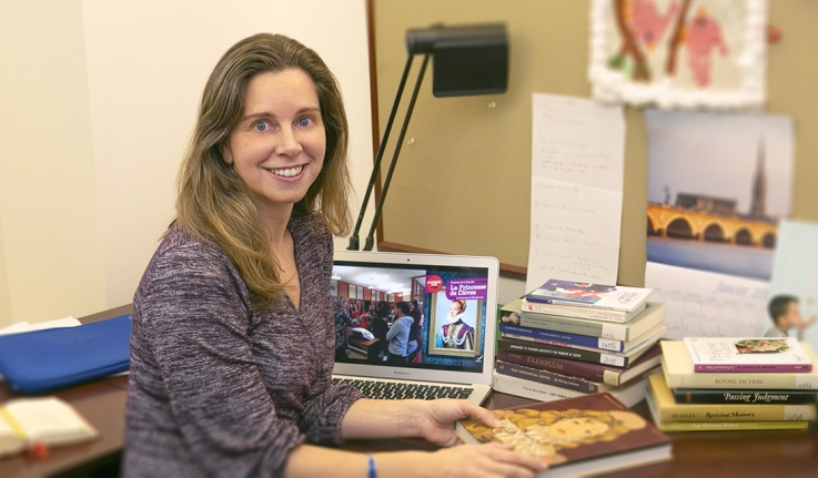 Helene Bilis sits at her desk in the Newhouse Center
