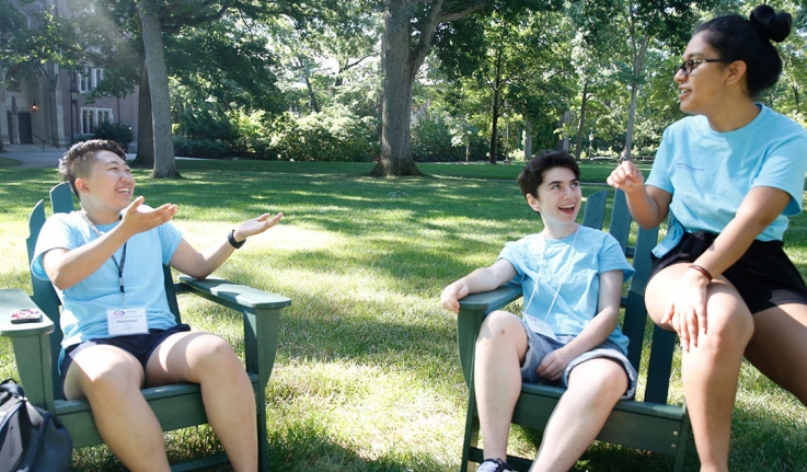 Three students sit at the Academic Quad in Adirondack Chairs, talking.