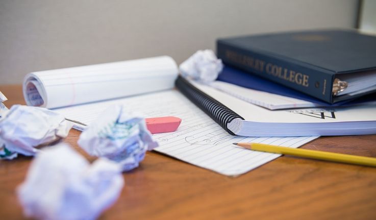 crumpled paper next to notebooks and a Wellesley binder