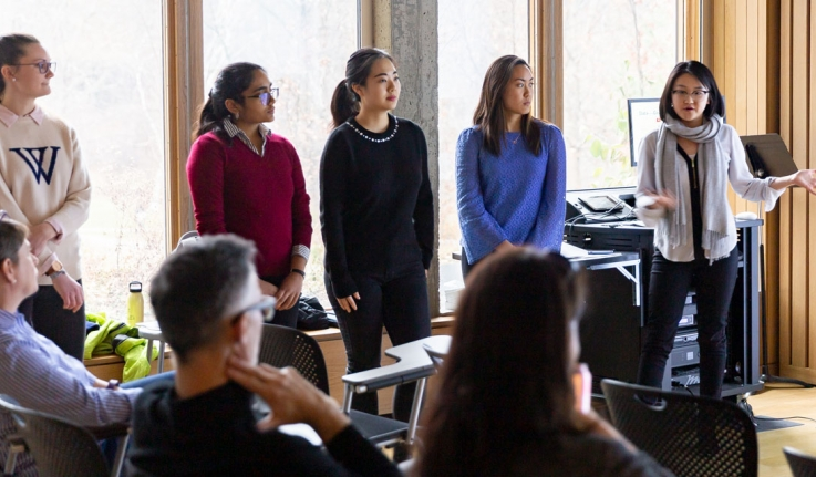 "Five students present a project in front of a crowd. One wears a Wellesley ""W"" sweater."