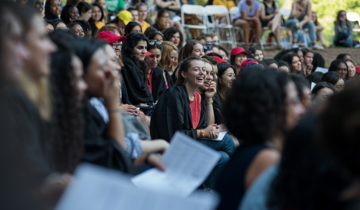 A student laughs amid a crowd of students in the theater