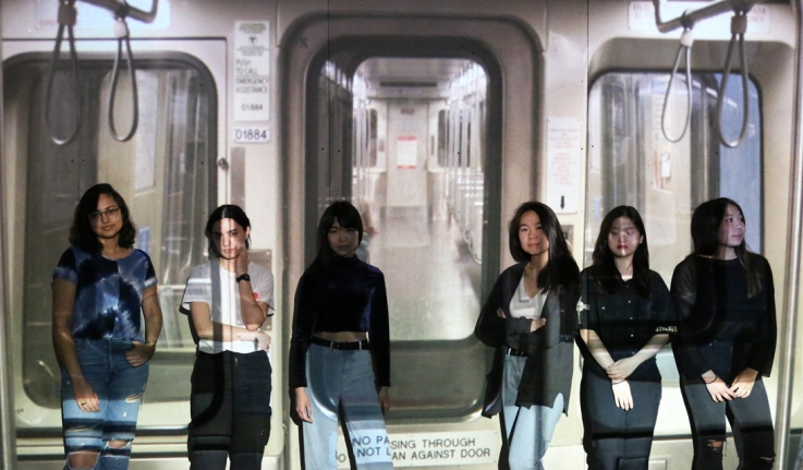 Six students stand in front of an art installation that depicts the inside of the MBTA's Red Line.