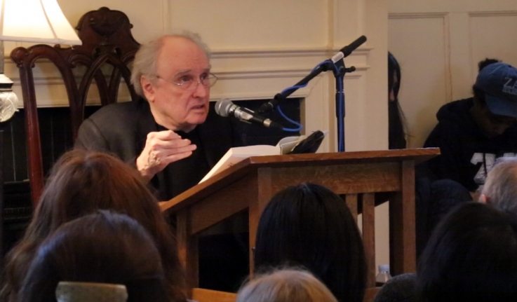 Frank Bidart sits at the front of a lecture room, reading from his Pulitzer Prize winning collection of poems.