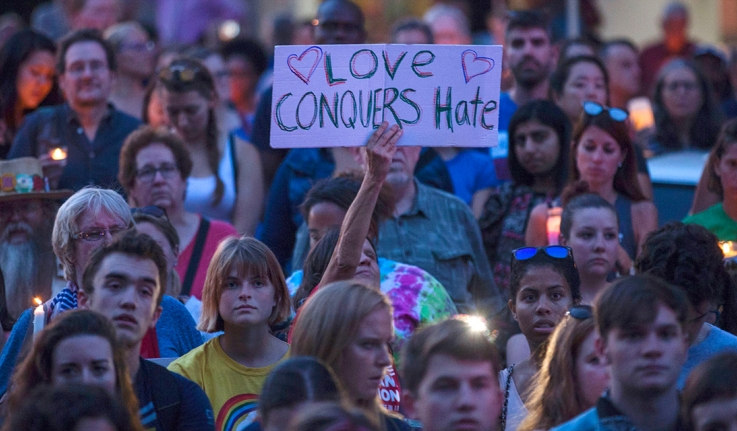 """Among a crowd gathered for a vigil, a woman holds a sign that says, """"Love Conquers Hate."""""""