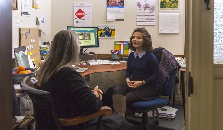 Emily Moss sits in conversation with a woman in an office.