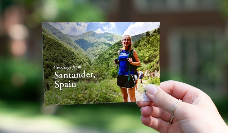 """A student stands in a Wellesley shirt in front of a mountain range in Spain. Text reads, """"Greetings from Santander, Spain"""""""