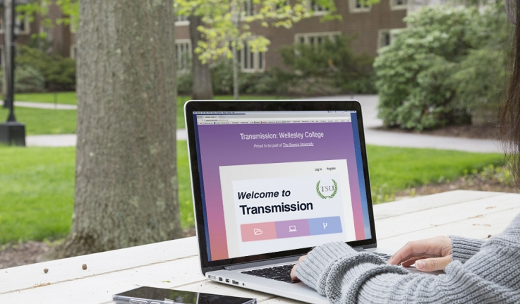 "A student sits at a picnic table in the academic quad looking at the screen of a laptop that reads, ""Welcome to Transmission"""