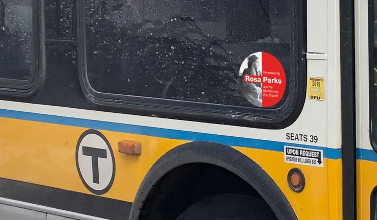 A MBTA bus with a sticker of Rosa Parks by the door.