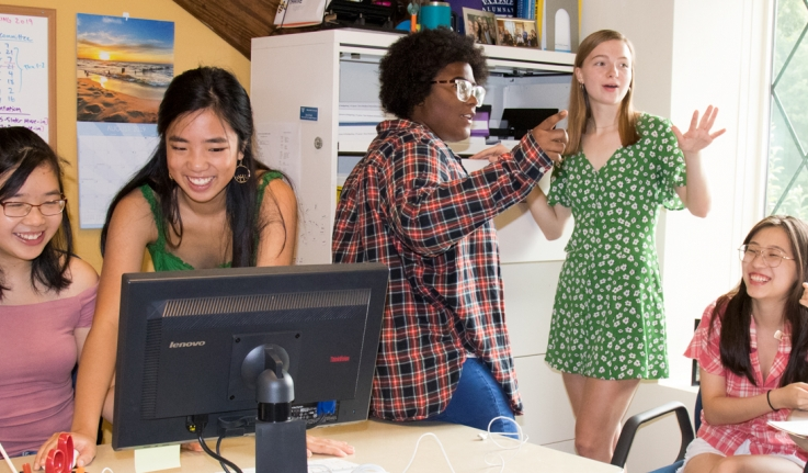Five students work in an office, preparing for orientation 2019.