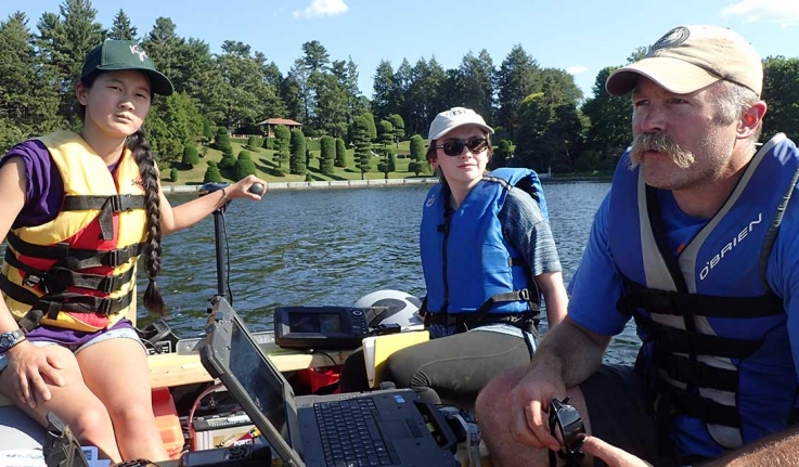 Two students and a visiting professor collected geological data from a boat on Lake Waban.