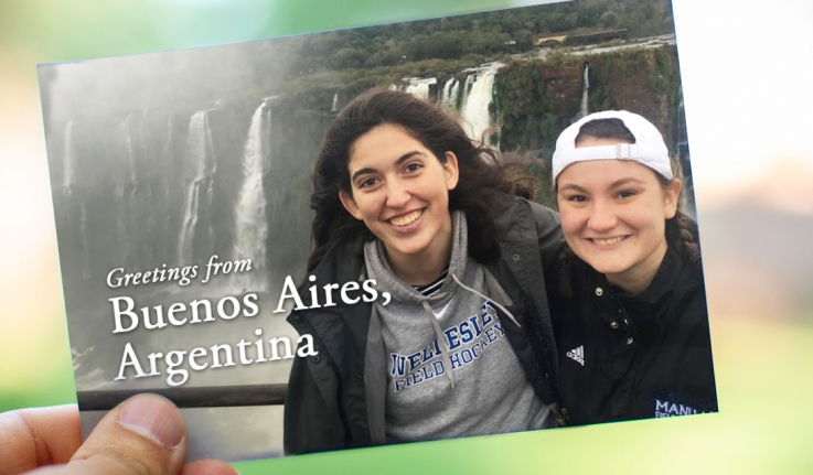 """On a postcard, two students stand in front of a waterfall in Buenos Aires. It reads, """"Greetings from Buenos Aires, Argentina!"""""""