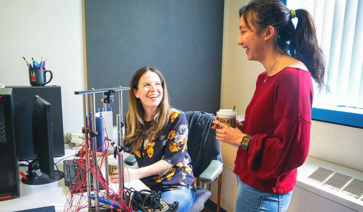A professor and student work together in a lab space.