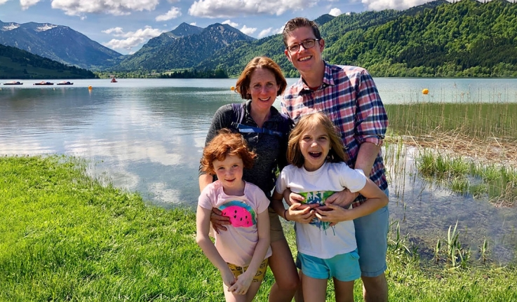Two professors and their daughters stand in front of a lake.