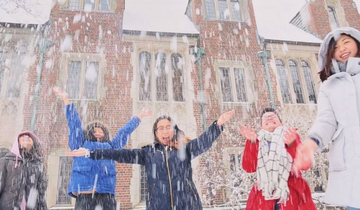 five students jumping joyfully in the snow