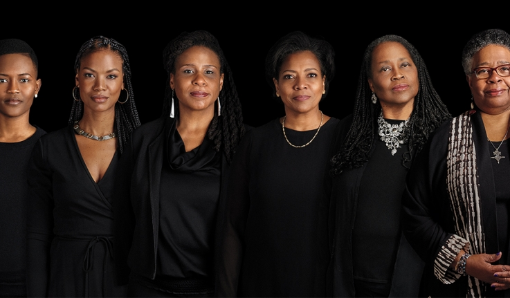 Six leaders of Ethos at Wellesley wearing black stand against a black backdrop looking directly at the camera.