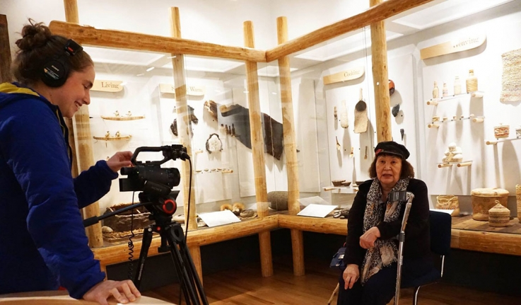One woman interviews another with a camera