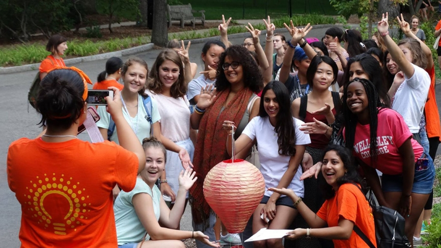 A group of students pose with a prize found during their orientation. A student takes their photo