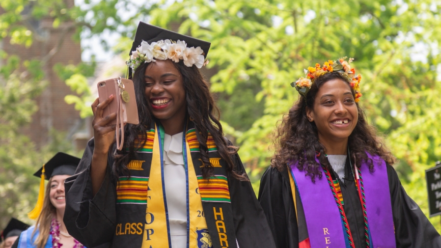 Two members of the class of 2019 walk into the tent for the commencement exercises.