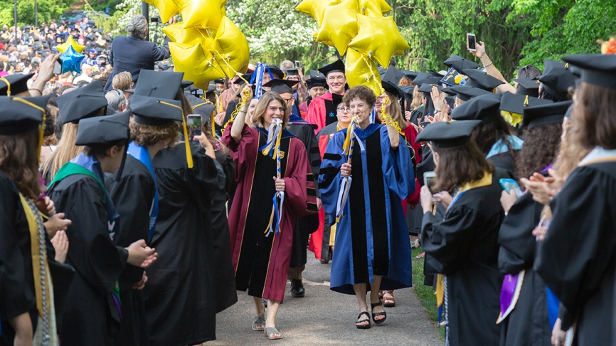 Class deans process in carrying yellow star balloons