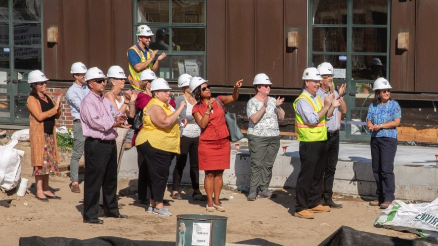 Wellesley community members and the construction team looks on as the beam is lifted into place.