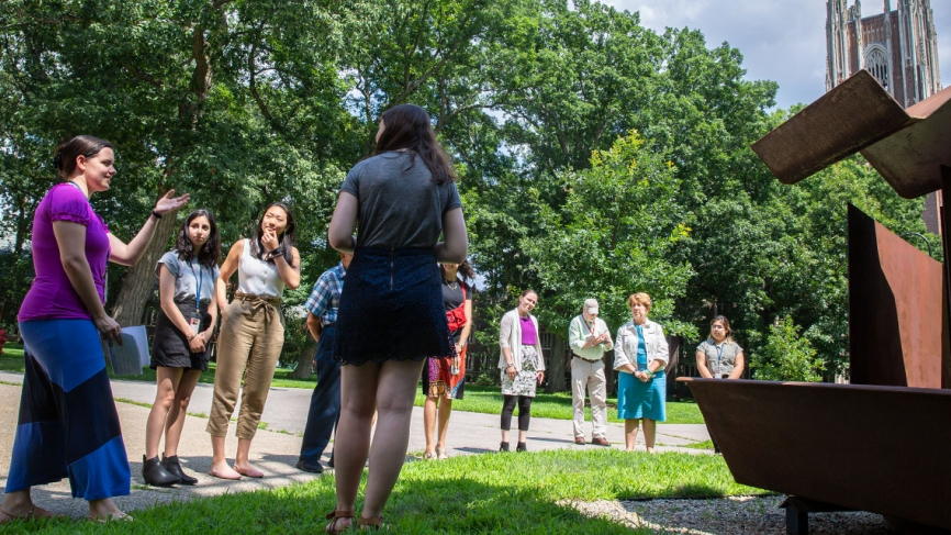 A student describes a sculpture in the academic quad