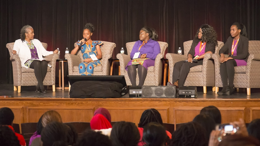 Four female students sit on a stage with a moderator, answering questions.