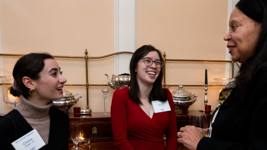 A student in a red shirt laughs with a dean and another student.