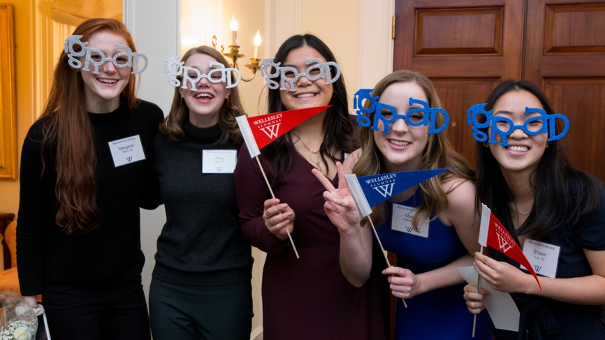 "Five students pose for the camera wearing ""grad glasses"" and holding Wellesley alumnae pennants"