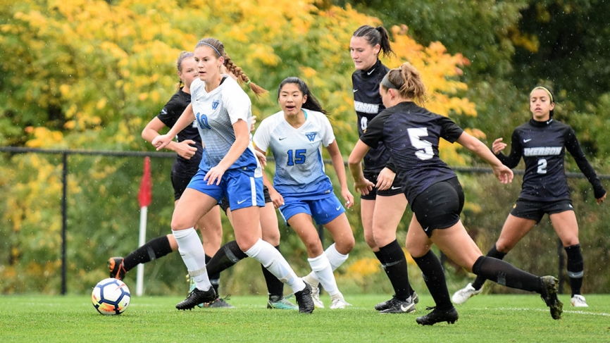 A Wellesley soccer player breaks from the pack with the ball.