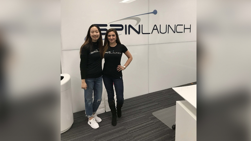 """Two women stand in front of branding that says """"SpinLaunch."""""""