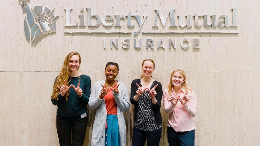"""Four women stand in front of a logo that reads """"Liberty Mutual."""" Their hands are in the shape of a W"""