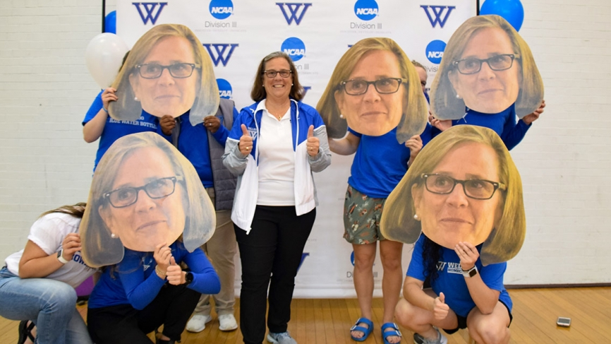 Bridget stands with a half dozen individuals who hold large cutouts of her face in front of their own
