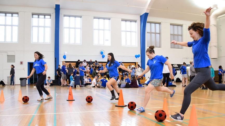 Students kick soccer balls inside a gym
