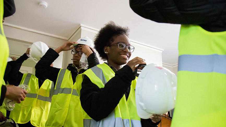 A students smiles as she puts on a hard hat.