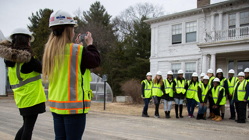 Students stand outside a white building posing in vests and constructions hats.