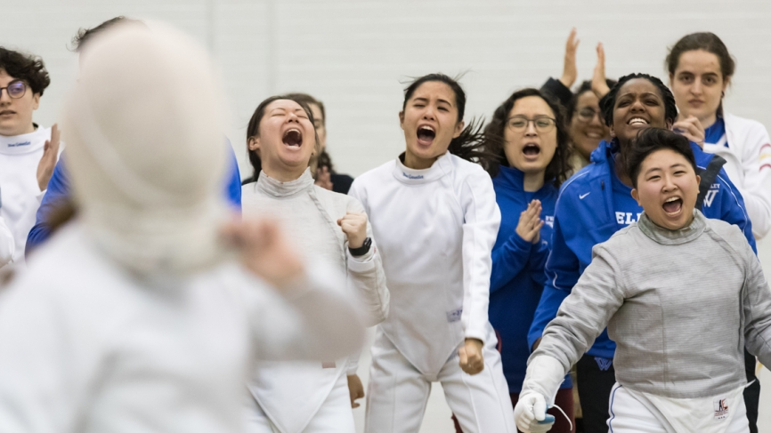Members of the Wellesley fencing team cheer for a teammate on the sidelines.