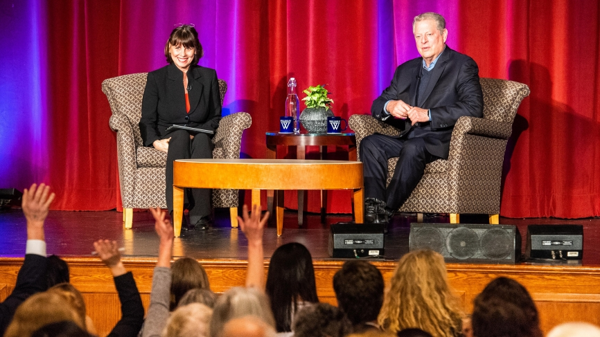 Al Gore and Sue Wagner sit on stage in front of a packed audience.