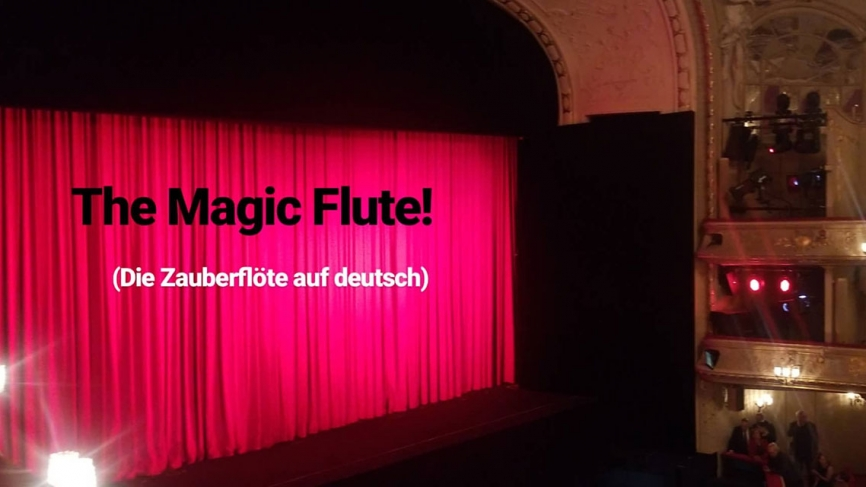 """The stage at the Berlin State Opera with a closed red curtain. Text reads, """"Magic Flute"""" (Die Zauberflöte auf deutsch)"""