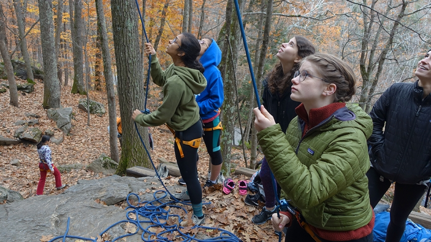 Students hold onto ropes before beginning to climb a boulder outdoors.
