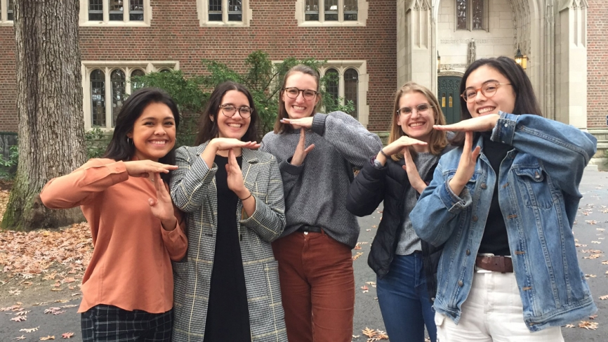 Outside Green Hall, 5 students pose for a photo making a T sign with their hands.